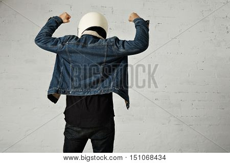 Back view on fit body of brutal younf motocyclist wears helmet, black longsleeve henley shirt and club denim jacket with his hands up