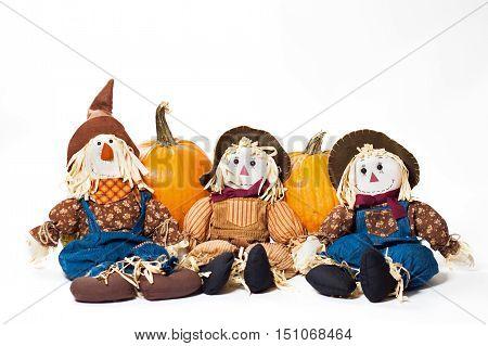 Three autumn scarecrows with pumpkins on white.