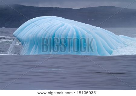Blue colored Iceberg with water flowing over.