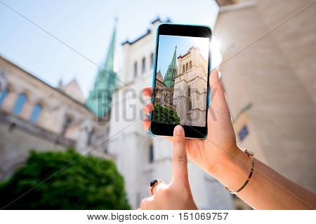 Photographing with phone famous Saint Pierre church in the old town of Geneva city in Switzerland