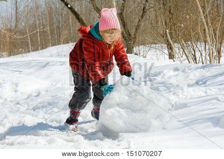 Girl Rolls A Snowball