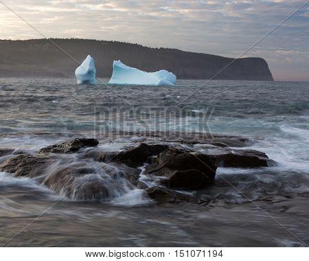 Coastal seascape with rocks and iceberg at sunset.