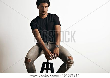 Gloomy serious sexy latino model in blank black t-shirt and jeans sitting and looking suspiciously into camera against white background