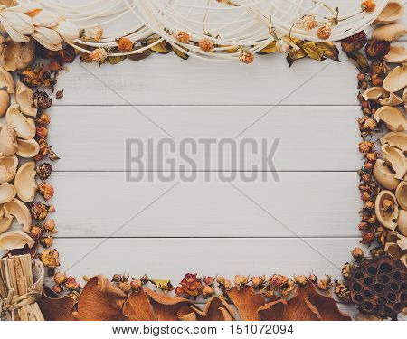 Fall decoration handmade frame concept background, top view with copy space on white wood table surface. Creative diy craft hobby, dried flowers, nut shells and other trinkets ornaments.