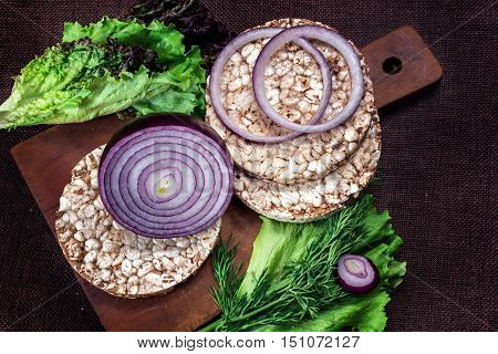 Puffed wheat cake, onions and lettuce on the kitchen table