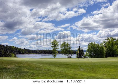 Green with water in the background on a beautiful golf course.