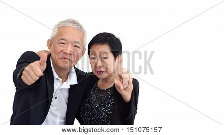 Asian Senior Couple In Business Attire Showing Hand Gesture Thumb Up And Pointing