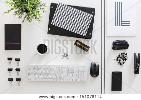 White desktop with esthetically ordered white and black stationery t-shirt