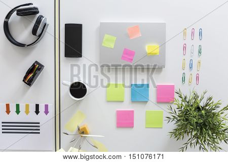 poster of Desktop with esthetically ordered statiorery clips multicoloured sticky notes and laptop