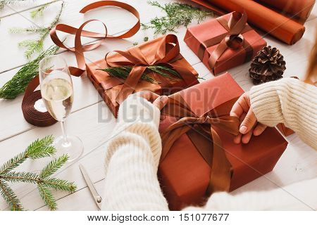Gift wrapping background. Female hands packaging stylish christmas present boxes in maroon paper decorated with satin ribbon bows. Christmas and winter holidays concept. POV