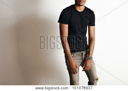 Mockup shot of a plain black cotton short sleeve t-shirt on an athletic black or latino man in a studio with white walls