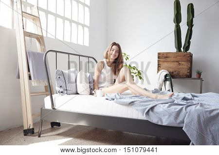Happpy Smiling Woman In Bed In Loft. Drinking Coffee