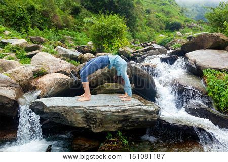 Yoga outdoors - young sporty fit woman doing Ashtanga Vinyasa Yoga asana Urdhva Dhanurasana  - upward bow pose at tropical waterfall