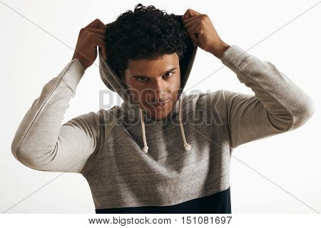 Attractive black man wears hoodie on his head with curly hair , looking miraculously on camera, isolated on white, close up