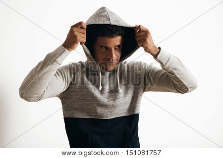 Attractive black man wears hoodie on his head with curly hair , looking miraculously on side, isolated on white