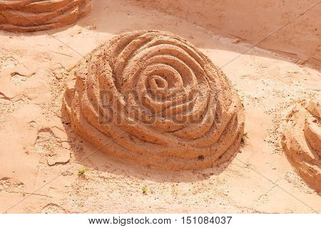 Sands sculpture in the form of a rose blossom on the beach