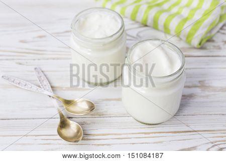 Homemade Yogurt In Glass Jar On Wooden Table.