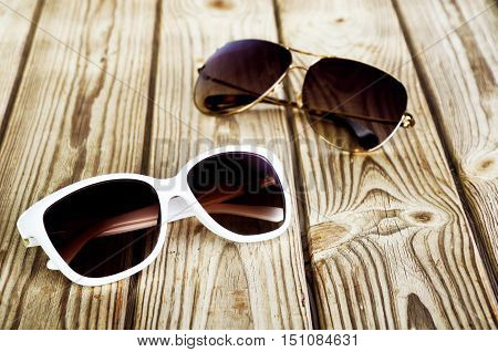 One White Female Sunglasses And One Unisex Sunglasses Close-up On A Wooden Background
