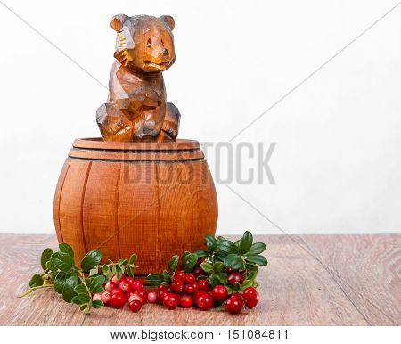 Wooden bear on small barrel with bunch of lingonberries on white background