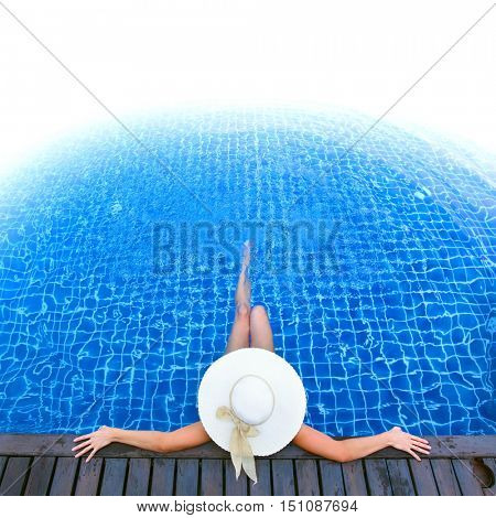Woman in sunhat relaxing at the pool, white copyspace