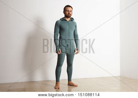 Young athlete wers green merino wool baselayer thermal suite in winter time, posing in front of white wall