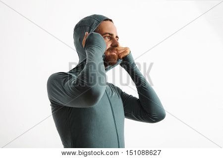 Bearded caucasian athlete fits hoodie of his wither snowboard baselayer thermal wear suite from merino wool