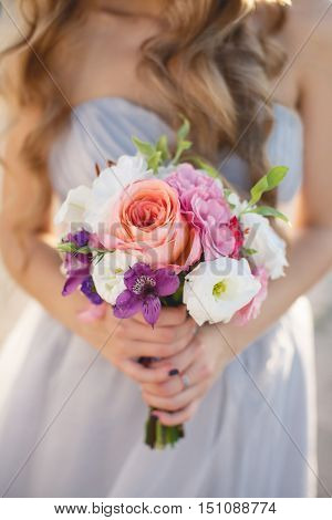 Beautiful wedding bouquet of assorted colors of white,pink,lilac and red colors in the hands of the bride dressed in white wedding dress,curly blond hair,the attention is focused on the bouquet of flowers