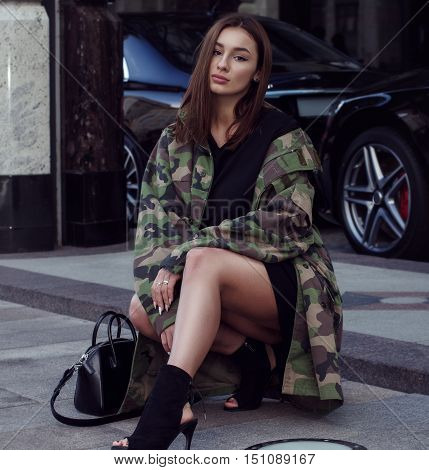 Fashionably dressed in military style girl sitting on his haunches