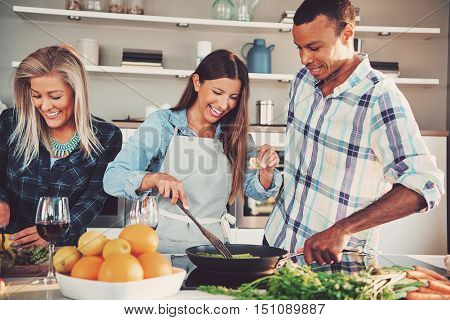 Three young adult friends frying food in pan together. Ingredients for the meal are in front of them.