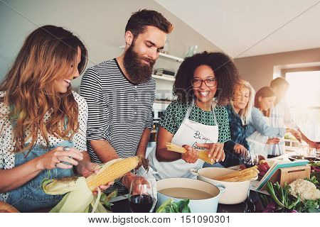 Happy group of young adult men and women cooking together at home in small kitchen or culinary classroom