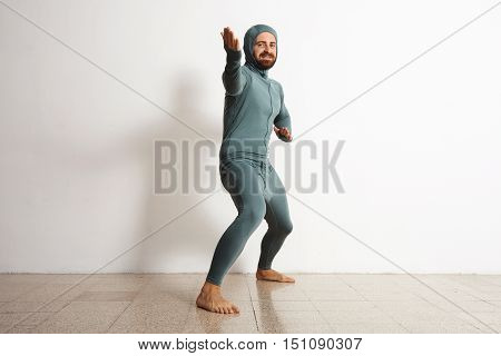 Happy smiling bearded fitted male wearing snowboarding thermal baselayer suite from merino wool and acts like a ninja in welcome position, isolated on white
