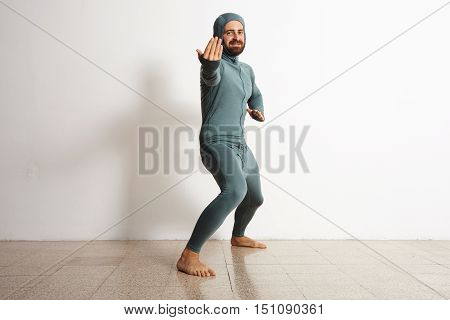 Happy smiling bearded sportsman wearing snowboarding thermal baselayer suite from merino wool and acts like a ninja, looking in camera, isolated on white