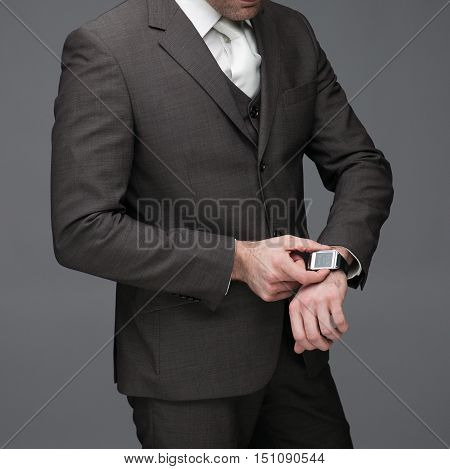 Business man adjusting his watch on a grey background stock picture
