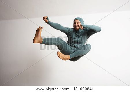 Young and fitted bearded athlete male wearing his winter snowboardint baselayer thermal suite and smiling acting like a ninja, jumping with leg kicks in air, focus on legs