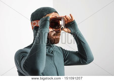 Portrait of bearded male athlete in baselayer thermal suite wears snowboarding googles