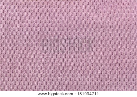 Pink background from soft fleecy fabric closeup. Texture of textile macro.