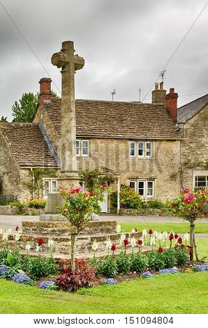 Stone cross in flower bed on grassy lawn in Castle Combe Village in Wiltshire, England.