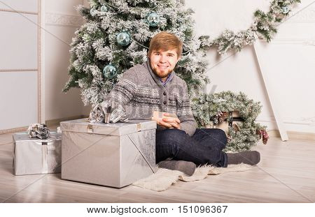 Holiday and special occasion. Man giving golden gift box with red ribbon isolated on white. Guy hiding present behind his back. Surprise. Studio shot.