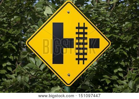 Railroad crossing sign up close yellow diamond.