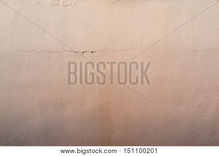 the abstract textured background of an old surface of the plastered wall of a motley apricot color tonality