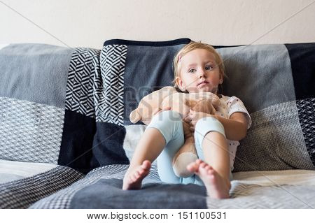 Cute little girl with her teddy bear at home sitting on sofa in living room
