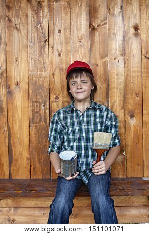 Boy painting the tool shed - taking a break in front of wooden wall