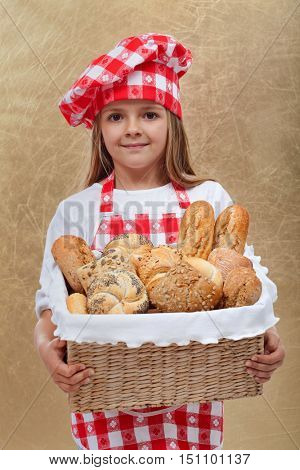 Little baker girl holding basket with fresh bakery products