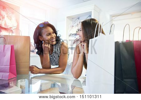 Two young woman in a clothing boutique leaning on the counter smiling and chatting as they wait to pay for their purchases lined up in bags