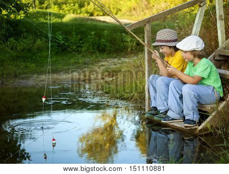 Happy boys go fishing on the river, Two children of the fisherman with a fishing rod on the shore of the lake