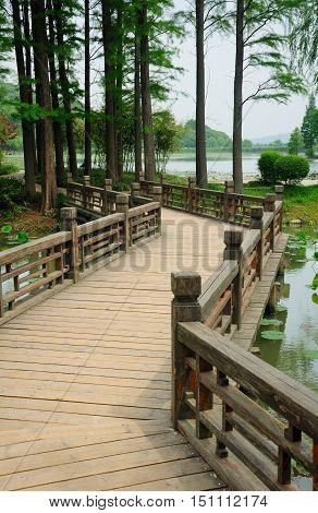 A wooden zig zag bridge over water at the Lake Tai (tai hu) scenic area on Turtle Island in Wuxi China in Jiangsu province.
