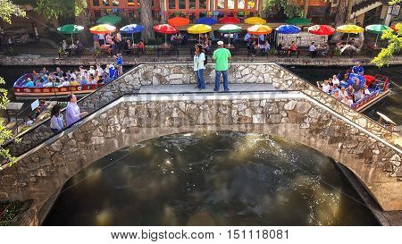 SAN ANTONIO, TEXAS - APRIL 14: A tour boat passes under a bridge with tourists at the historic San Antonio River Walk in downtown San Antonio, Texas on April 14th, 2016.