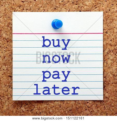 The words Buy Now Pay Later in blue text on a note card pinned to a cork notice board as a reminder to purchase on credit