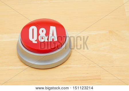 A Q&A red push button A red and silver push button on a wooden desk with text Q&A