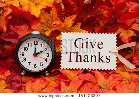 Give thanks message Some fall leaves and black and white alarm clock and beige gift tag with text Give Thanks